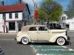A classic car passes a classic gas station-come-bike shop