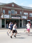 Runners pass the Dedham Community Theatre