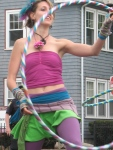 A young woman twirls a hula hoop
