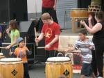 Young volunteers participate in a taiko drumming performance
