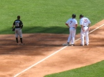Ballplayers stand in the shadow of the light standard.