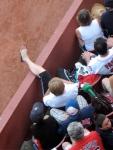 A fan gets cozy by the left field line.