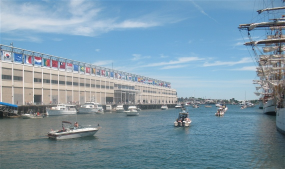 Pleasure boats loop around the dock to enjoy viewing the tall ships.