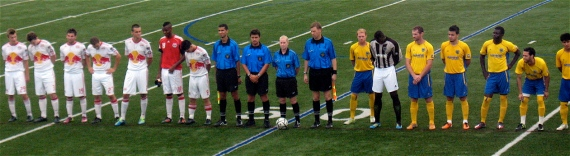 The teams and referees line up for the National Anthem.