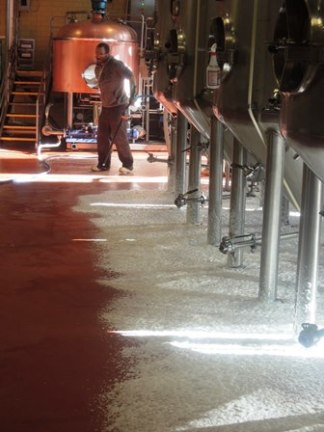 The most action in the brewery was this man spraying foam under the tanks.